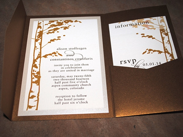 Gold pocket invitations with birch tree trunks